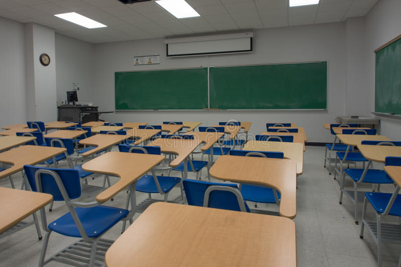 Empty Classroom. An empty classroom with blackboard and lecture chairs royalty free stock photography