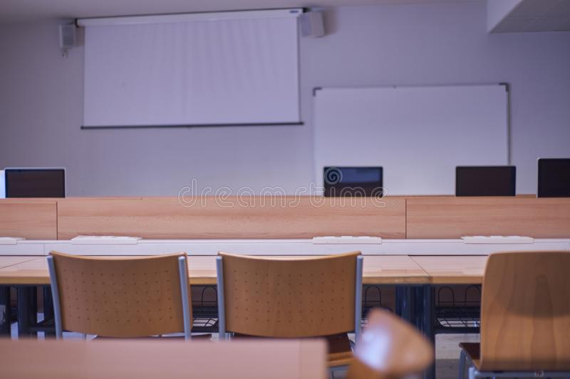 Empty classroom, with chairs, tables, with computers and projector screen.  stock image