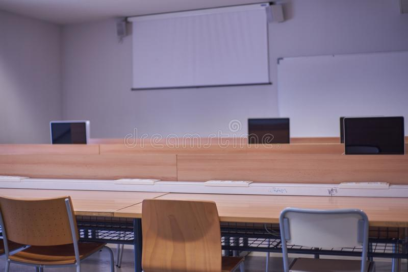 Empty classroom, with chairs, tables, with computers and projector screen.  royalty free stock image