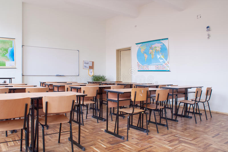 Empty classroom interior. With wooden desks and chairs, maps and white board royalty free stock photos