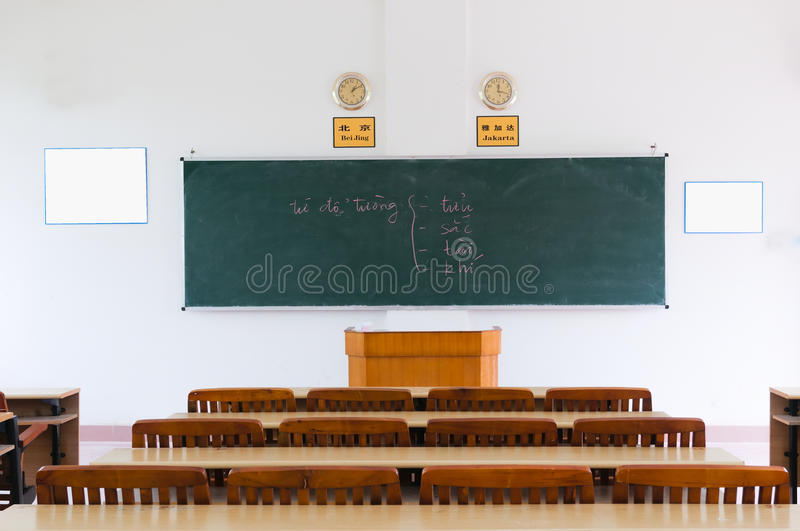 Empty Classroom. A large, empty classroom with wooden chairs stock photos