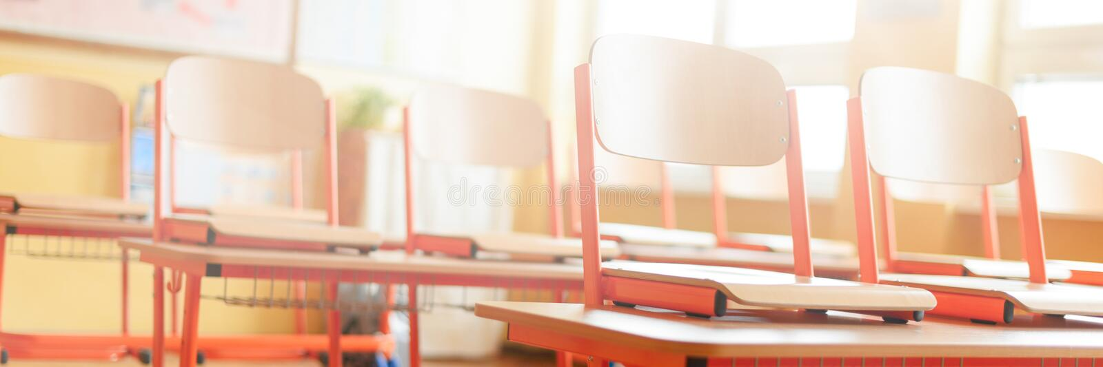 Empty classroom with school desks, chairs and blackboard. Education concept. Empty classroom with school desks, chairs and blackboard. Education concept stock image