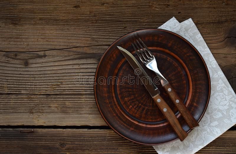 Empty clay plate, cutlery, napkin on wooden background. Table setting captured from above. Top view, flat lay. Rustic style. Copy stock images