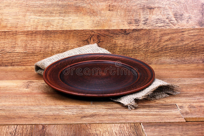 Empty clay plate. On a wooden background royalty free stock photos