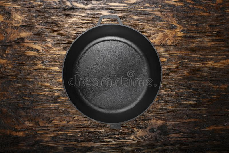 Empty clean cast iron skillet on a wooden background. Space for text stock images