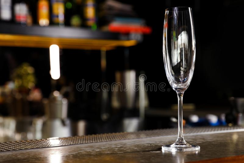 Empty clean champagne glass on counter in bar. Space for text royalty free stock images