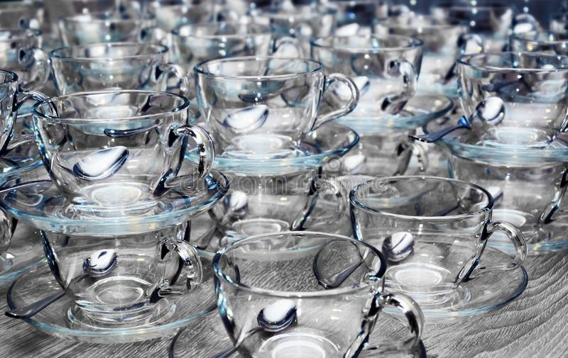 Empty clean glass transparent cups with saucers, teaspoons on gray wooden table. Catering, tea party preparation concept royalty free stock photography