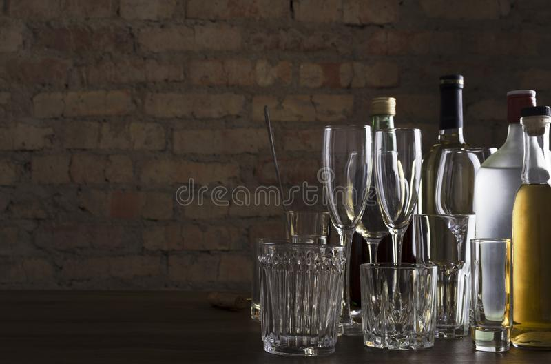 Empty clean glasses for wine, champagne, cocktails and bottles of alcoholic driks on the table agaisnt brick wall.Night at the bar royalty free stock photography