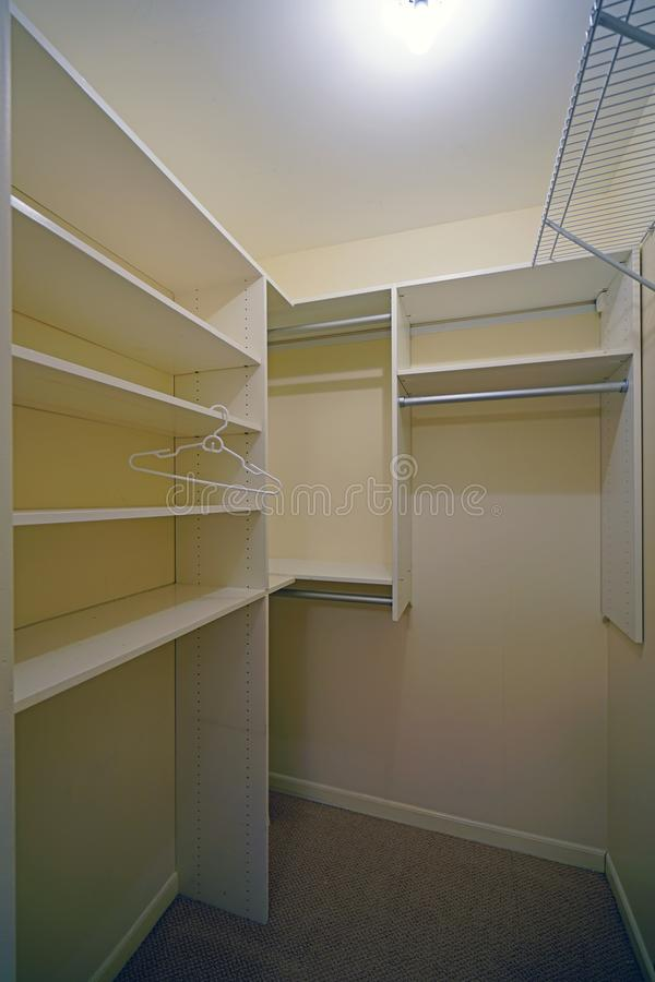 Empty clothes closet with shelves. Before a move in stock photography