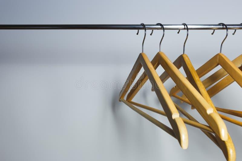 Empty coat hangers on a metal rack stock photo
