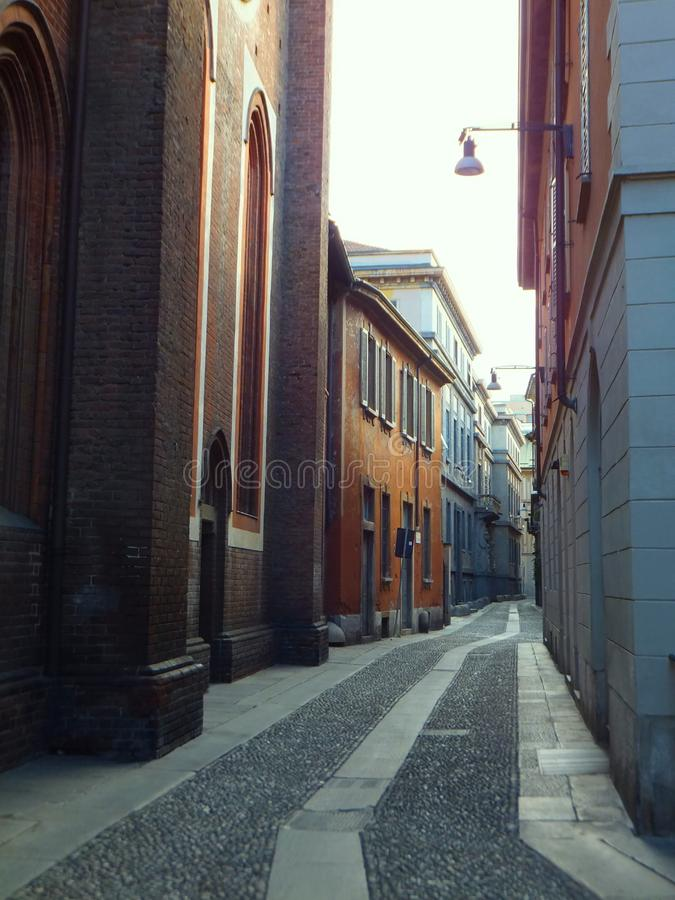 An empty cobbled street in Milan, Italy, lined with a church and old houses, leading with slight twists and turns into distance. An empty cobbled street in Milan stock photo