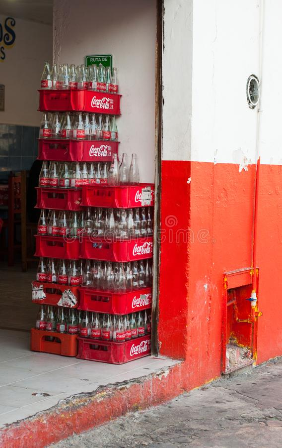 Empty Coca-Cola bottles in the crates at the entrance of small Mexican street cafe royalty free stock photography