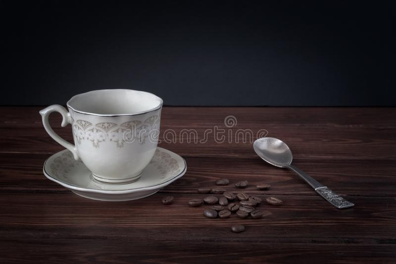 Empty coffee mug on a saucer, coffee beans on dark table boards. royalty free stock photos