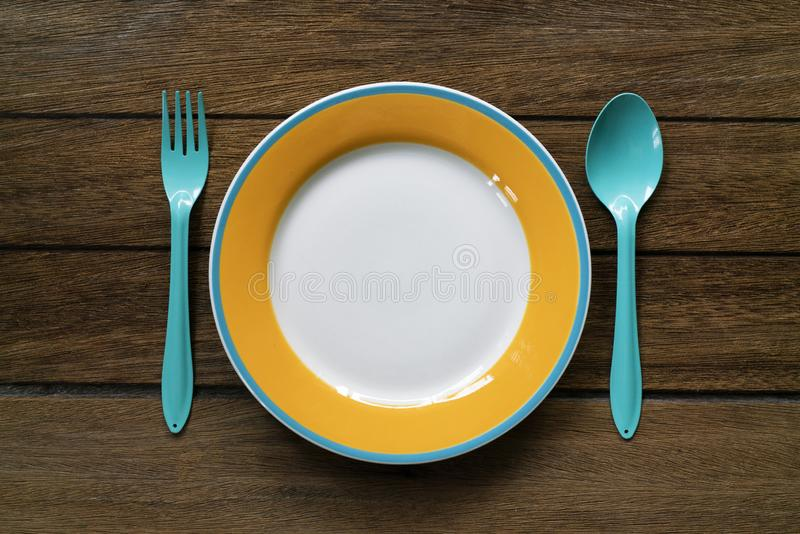 Empty color plate, fork and spoon on wooden table background royalty free stock photo