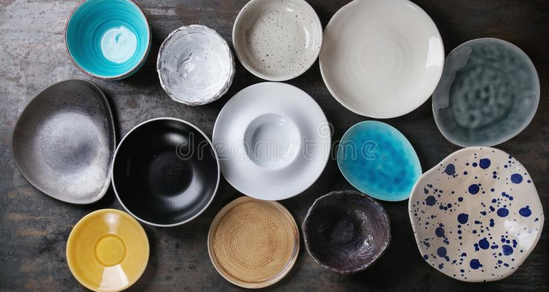 Empty colorful plates collection. Empty colorful modern ceramic plates and bowls collection. Various of dishware over dark metal background. Top view royalty free stock images