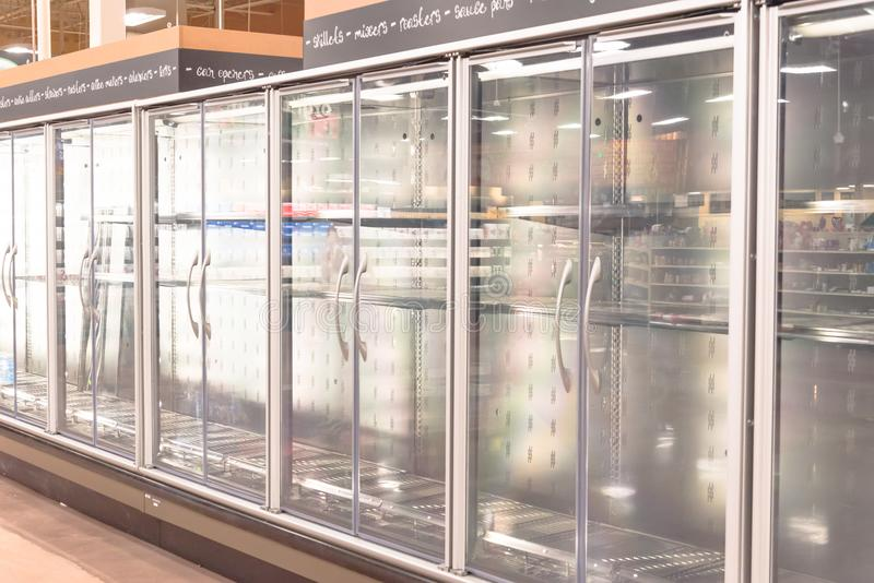 Empty commercial fridges at grocery store in America. Sold out frozen food section royalty free stock image