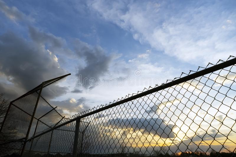 Empty community baseball diamond and fence in silhouette against. A sunset sky at dusk stock images