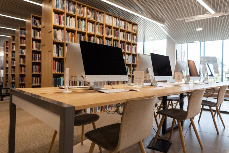 Empty computer room in the school library. Modern computers stand on a wooden table. stock photos