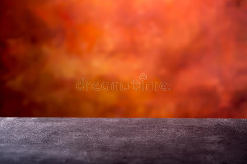 Empty concrete table and abstract batik orange- red background ready for photomontage. Empty space for your products. Empty concrete table and abstract batik stock photo