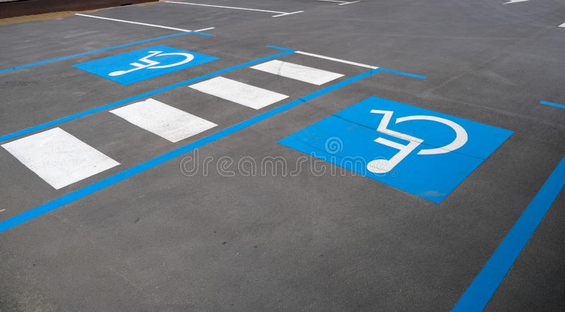 Empty convenient parking for cars with places for disabled people. Disabled parking divided by a pedestrian crossing. Empty convenient parking for cars with stock photos