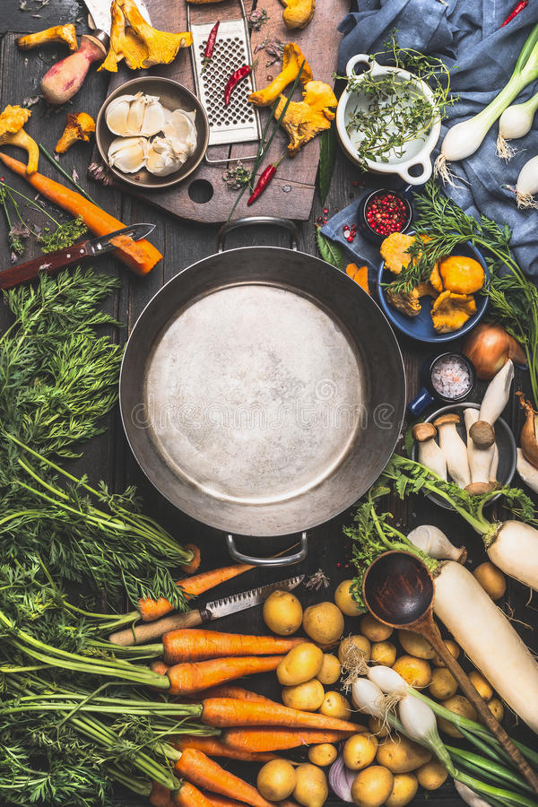 Empty cooking pot and vegetables ingredients for cooking, dark style, top view royalty free stock photo