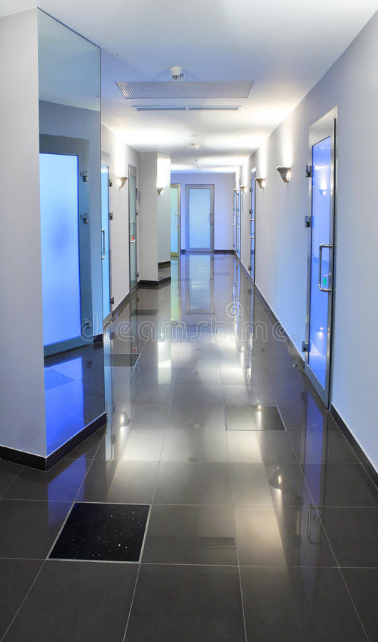 Empty corridor in a hospital or office building. Long, empty corridor in a hospital or office building, with the ceiling lights reflected on the shiny floor stock photography