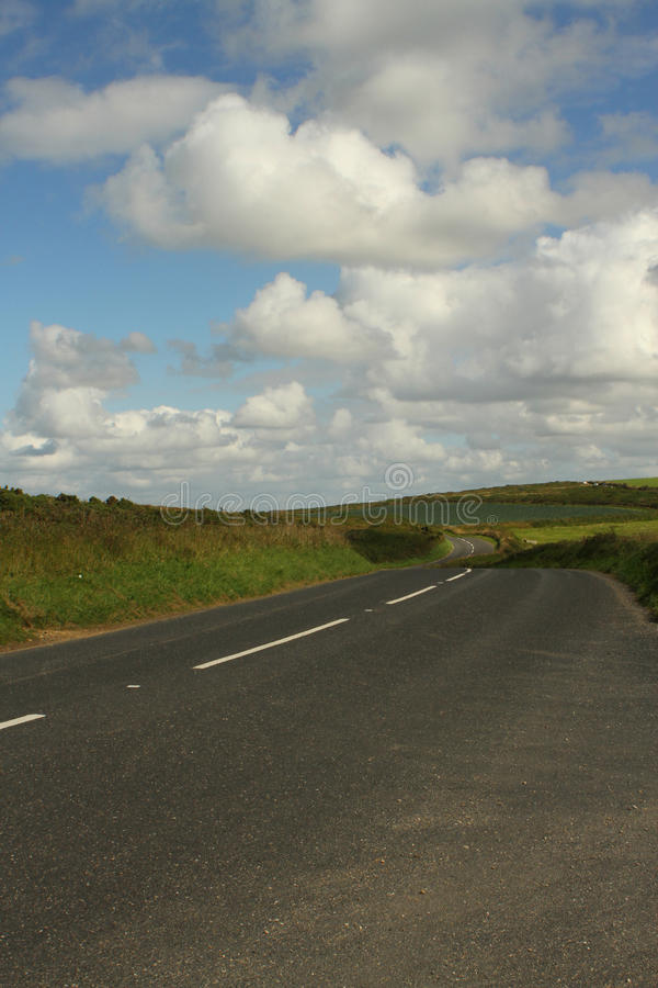 Empty country road. Empty winding country road with rolling green hills, blue sky and white clouds, a road less travelled royalty free stock photos