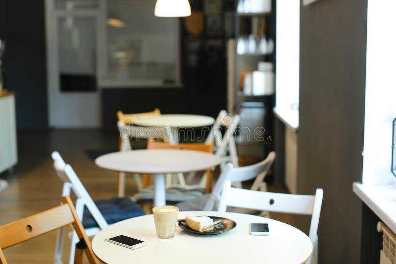 Empty cozy cafe with cups of coffe, smartphones and cake on table. Concept of interior and catering establishment, modern technology stock image