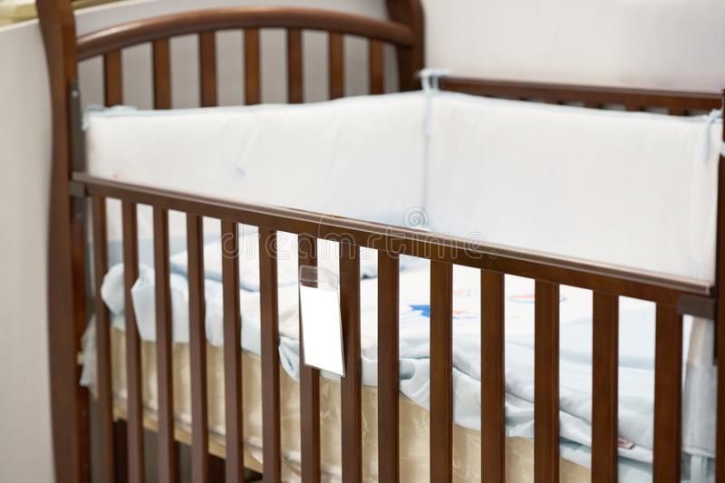 Empty crib with pillow and price slip label. In mall stock photo