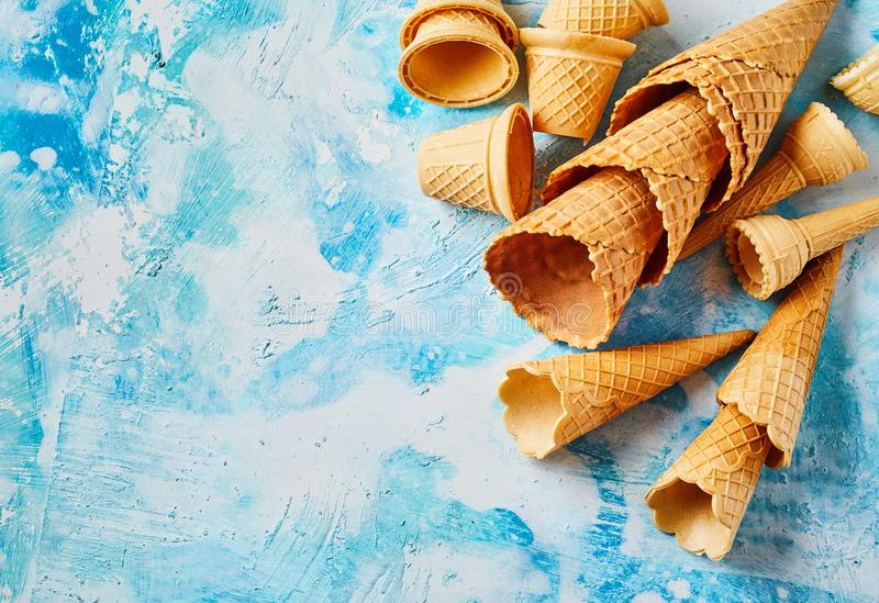 Empty crunchy wafer cones on blue background stock image