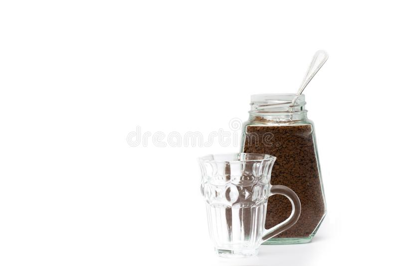 Empty crystal coffee mugs, coffee spoons and coffee in a glass bottle. On a white background royalty free stock photography