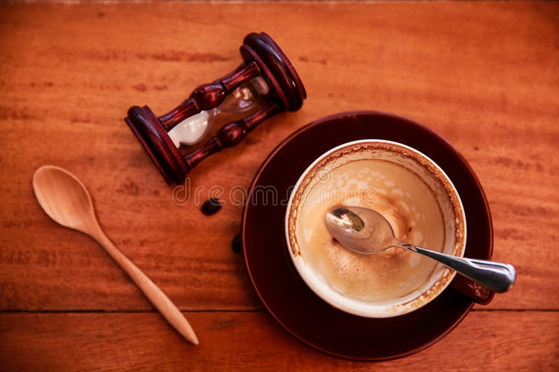 Empty cup of coffee with spoon and sand glass on wooden table wooden background, royalty free stock photos