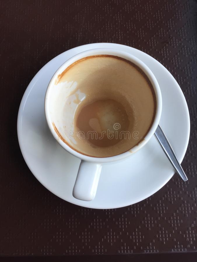 Empty cup of coffee and spoon. On table stock photo