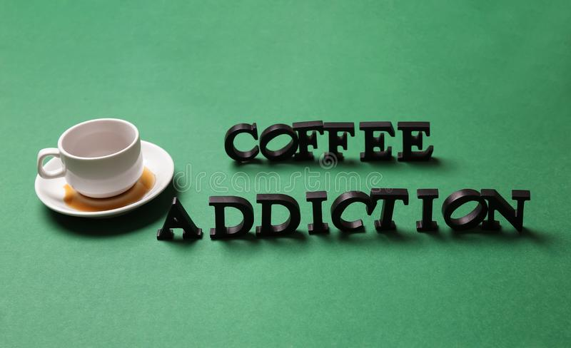 Almost empty cup of coffee with text COFFEE ADDICTION on color background royalty free stock photo