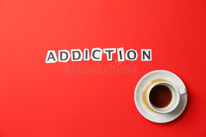 Almost empty cup of coffee with word ADDICTION on color background royalty free stock photo