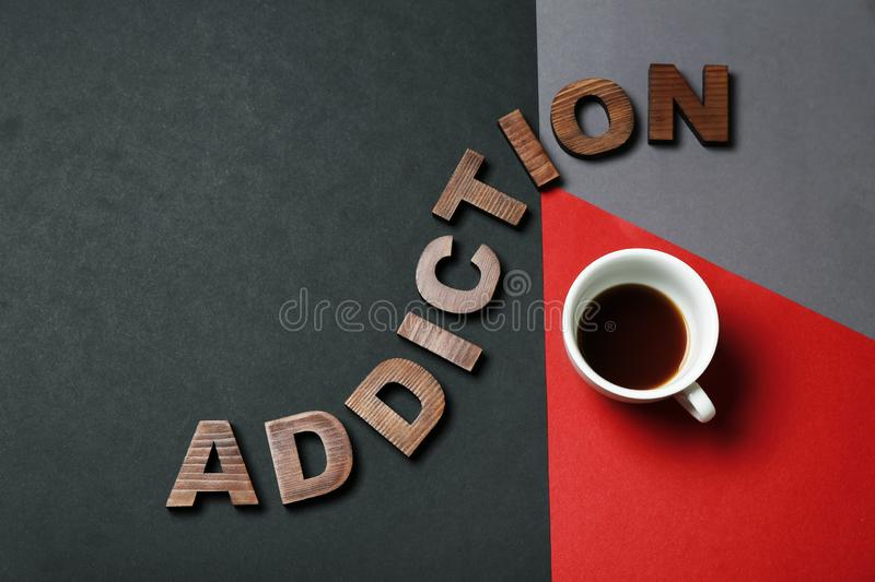 Almost empty cup of coffee with word ADDICTION on color background royalty free stock image