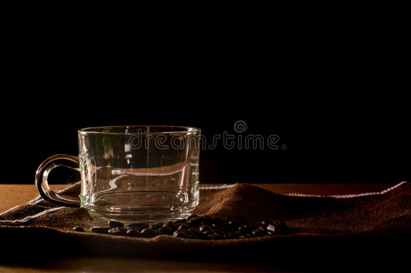 Empty cup and group of coffee beans on brown table cloth with black background with copy space for your text. Benefits of coffee. Concept royalty free stock images