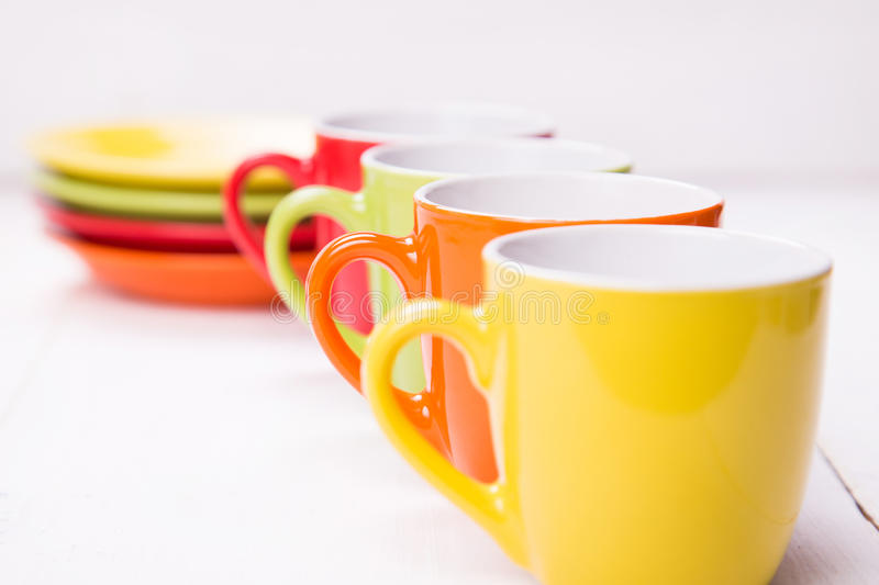 Empty cup. Some colored empty cups on white wooden background royalty free stock image