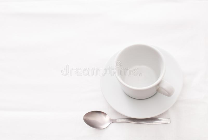 Empty white Cup of tea with spoon on white. An empty Cup of tea on the table with a white tablecloth. Place for text. Background image stock photos