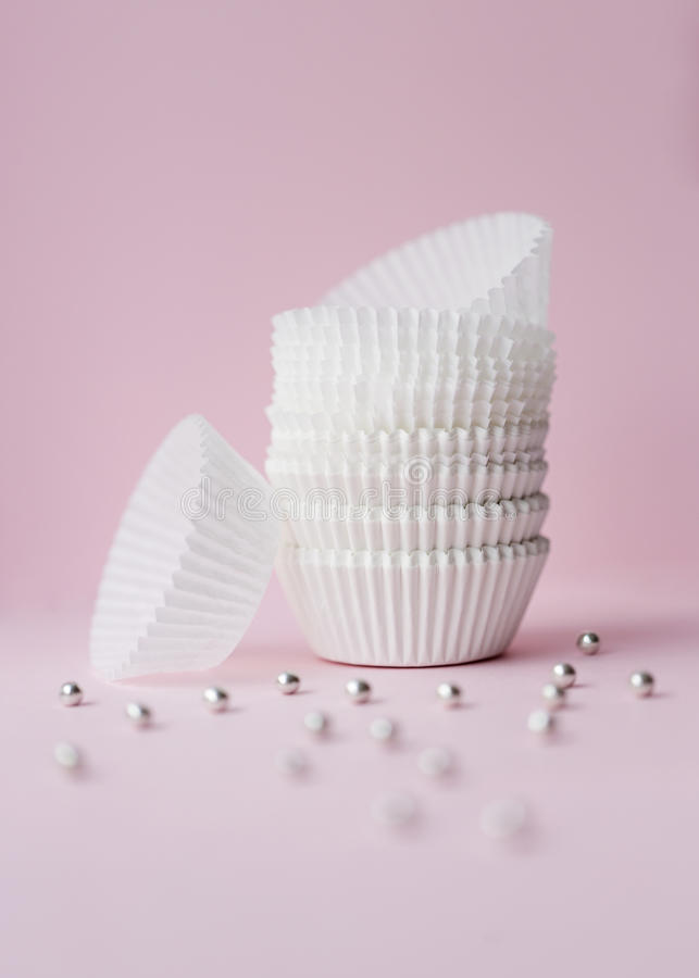 Empty cupcake wrappers on pink royalty free stock photo