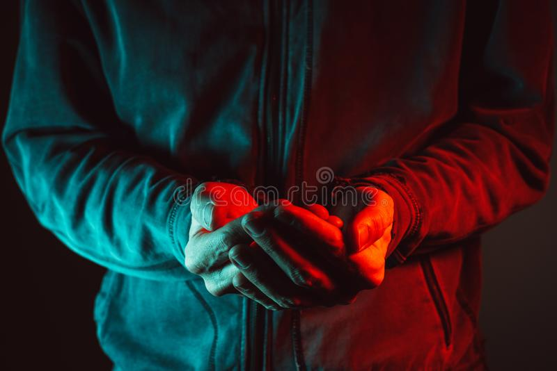 Empty cupped male hands pleading and begging. Low key red and blue light photography royalty free stock images