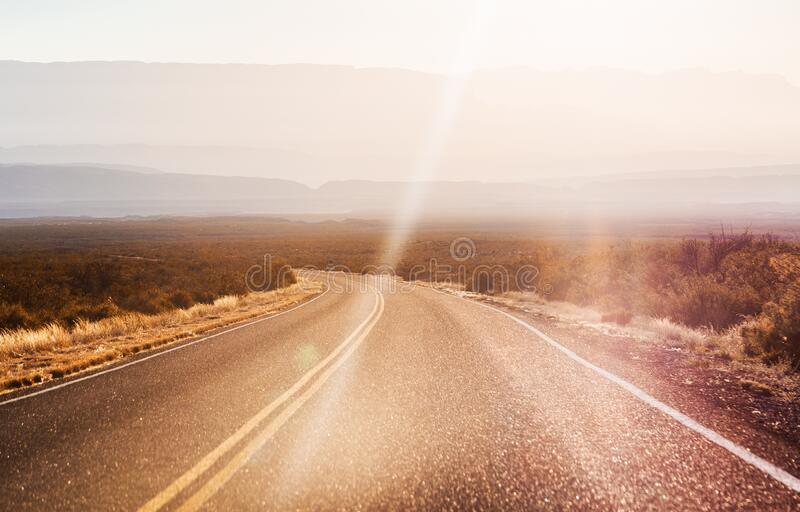 Empty curving road. An empty curving road with hazy hills in the background stock photography