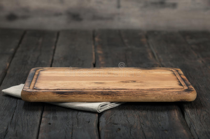 Empty cutting board with cloth napkin on wooden table royalty free stock photography