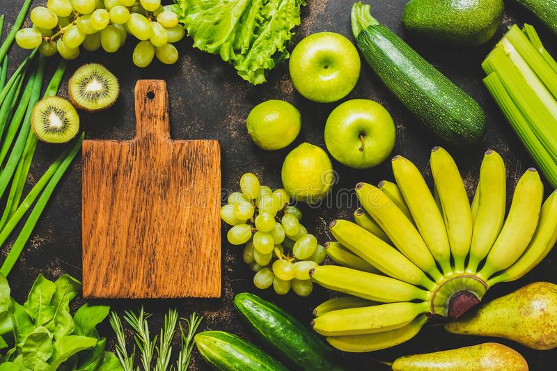 An empty cutting board and a frame of fresh green and yellow vegetables and fruits. Top view. Various vegetables and fruits. royalty free stock photography