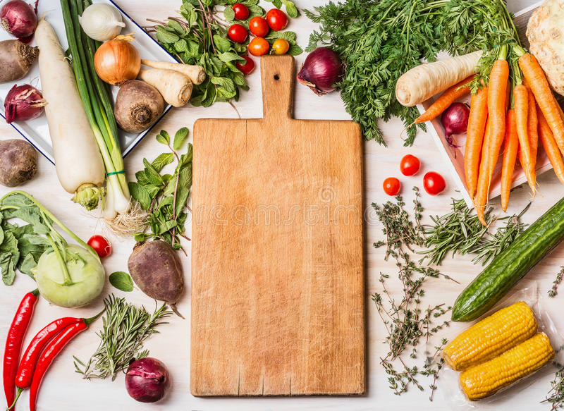 Empty cutting board and various raw vegetables for tasty and healthy cooking, top view, place for text,. Frame. Vegan or vegetarian food concept royalty free stock photos