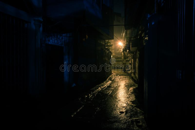 Empty and dangerous looking urban back-alley at night time in suburbs Hanoi royalty free stock photo