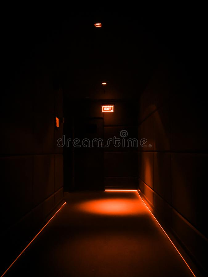 Empty dark corridor illuminated with orange lights in a building royalty free stock photography
