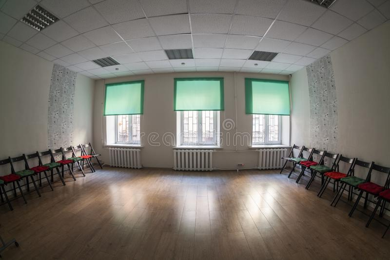 Empty dark room with three windows on wall, chairs standing on the sides and wooden hardfloor, nobody. Empty dark room with three windows on wall, chairs stock image