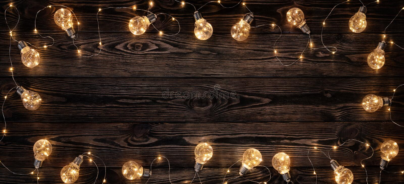 Wooden background illuminated by retro light bulbs stock photography