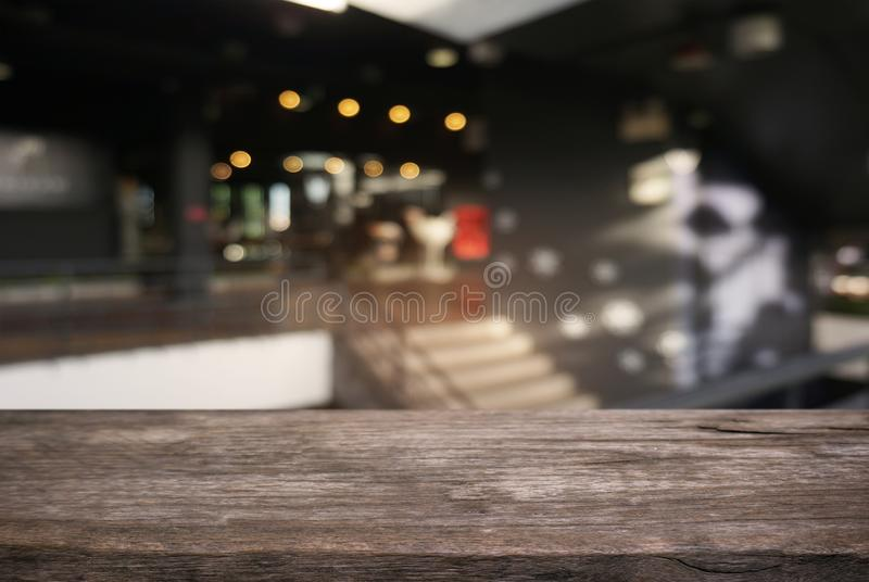 Empty dark wooden table in front of abstract blurred background. Of cafe and coffee shop interior. can be used for display or montage your products royalty free stock images